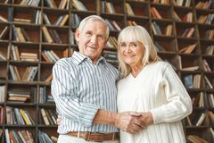 Senior couple together at home retirement concept standing holding hands looking down camera. Aged man and woman together at home in the living room standing stock photos