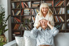 Senior couple together at home retirement concept surprise cheerful. Aged men sitting and women standing closing his eyes together at home in the living room royalty free stock photos