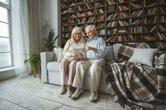 Senior couple together at home retirement concept using digital tablet pointing at screen. Aged men and women together at home in the living room sitting on the stock photography