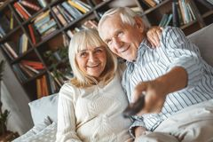 Senior couple together at home retirement concept watching tv switching channels royalty free stock image