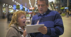Senior couple with touch pad at the airport. Senior woman explaining something to her husband using tablet computer at the airport stock footage
