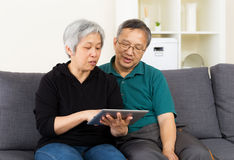 Senior couple with touchpad sitting Royalty Free Stock Images