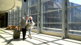 Senior couple of tourists. Walking with suitcase in airport and talking stock footage