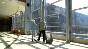 Senior couple of tourists. Walking with suitcase in airport and talking stock video