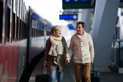 Senior couple on train station pulling trolley luggage. Royalty Free Stock Image