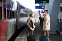 Senior couple on train station pulling trolley luggage, waving. Royalty Free Stock Image