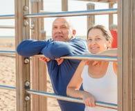Senior couple training on pull-up bar Royalty Free Stock Photos