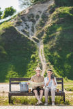 Senior couple of travelers sitting together on bench and holding map and instant camera Stock Photo