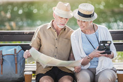 Senior couple of travelers sitting together on bench and holding map and instant camera Royalty Free Stock Photo