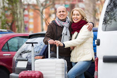 Senior couple of travellers posing with trollers Royalty Free Stock Photos