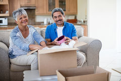 Senior couple unpackaging cardboard box in living room at home Royalty Free Stock Image