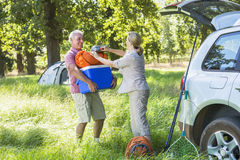 Senior Couple Unpacking Car For Camping Trip In Countryside Stock Image