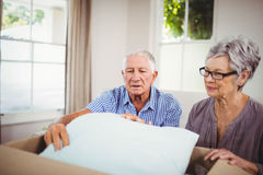 Senior couple unpacking a cardboard box. In living room Royalty Free Stock Photography