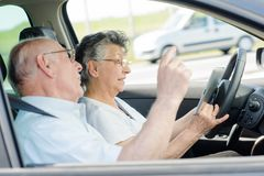 Senior couple using cellular while driving royalty free stock images