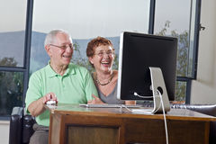 Senior couple using  computer. Senior couple using an imac computer Royalty Free Stock Photo