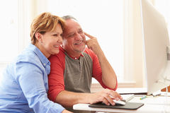 Senior Couple Using Computer At Home Stock Images