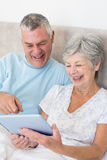 Senior couple using digital tablet in bed Royalty Free Stock Image