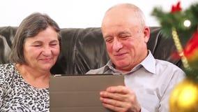 Senior couple using digital tablet at Christmas stock video