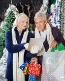 Senior Couple Using Digital Tablet At Christmas Royalty Free Stock Image