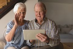Senior couple using digital tablet. Front view of a senior couple using digital tablet in living room at home stock photo