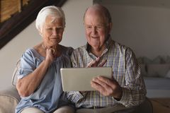 Senior couple using digital tablet. Front view of a senior couple using digital tablet in living room at home stock image