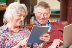 Senior Couple Using Digital Tablet And Laptop At Home Stock Images