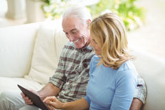 Senior couple using digital tablet in living room. At home Stock Photography