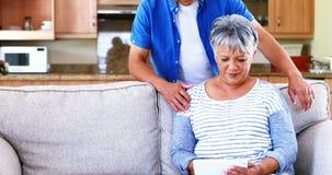 Senior couple using digital tablet in living room 4k stock video