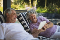 Senior couple using digital tablet on lounge chairs Stock Photo