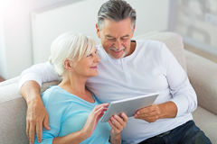 Senior couple using digital tablet. Loving senior couple at home Royalty Free Stock Images