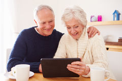 Senior Couple Using Digital Tablet At Table Royalty Free Stock Photography