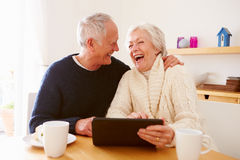 Senior Couple Using Digital Tablet At Table Stock Photos