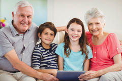 Senior couple using digital tablet with their grand children. Portrait of senior couple and their grand children using digital tablet in living room Royalty Free Stock Images