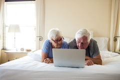Senior couple using laptop on bed in bedroom Royalty Free Stock Images