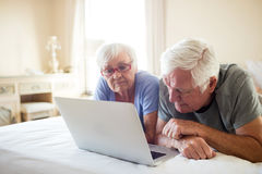 Senior couple using laptop on bed in bedroom Stock Images