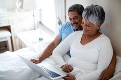 Senior couple using laptop in bedroom Stock Photo