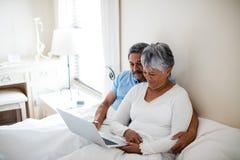 Senior couple using laptop in bedroom Stock Photos