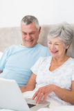 Senior couple using laptop computer in bed Stock Photos