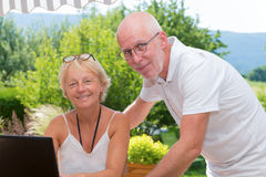 Senior couple using laptop computer at home. A senior couple using laptop computer at home, outdoors Royalty Free Stock Photo