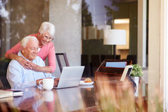 Senior Couple Using Laptop On Desk At Home stock photo