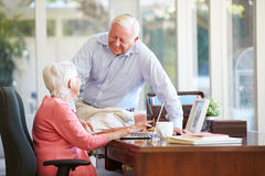 Senior Couple Using Laptop On Desk At Home Royalty Free Stock Images