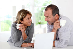 Senior couple using laptop and drinking coffee Royalty Free Stock Photos