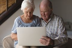 Senior couple using laptop. Front view of a senior couple using digital tablet in living room at home royalty free stock photos