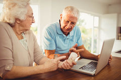 Senior couple using laptop and holding pills Stock Photos