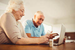 Senior couple using laptop and holding pills Stock Images