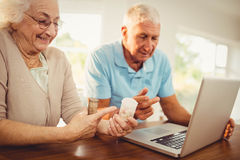 Senior couple using laptop and holding pills Royalty Free Stock Photos