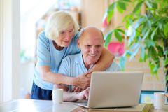 Senior couple using laptop at home. Two smiling people, active senior couple, drinking coffee from cups and enjoying modern technology using laptop computer with Stock Photo