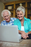 Senior couple using laptop in living room Royalty Free Stock Photography