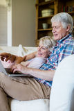 Senior couple using laptop in living room Royalty Free Stock Photos