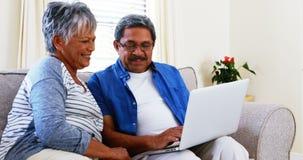 Senior couple using laptop in living room 4k